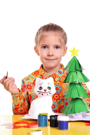 Girl with painted homemade toys and paper tree  스톡 콘텐츠