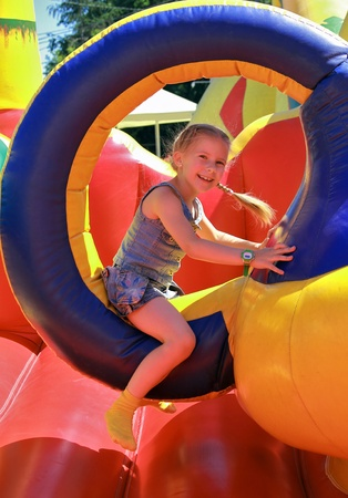 Joyful girl jumping on a trampoline inflatable   photo