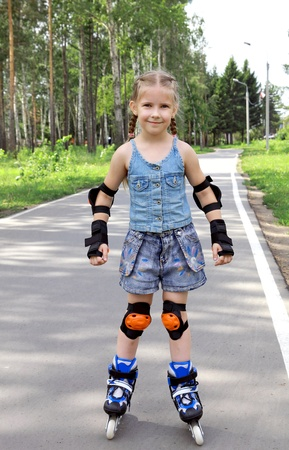 A girl learns to ride in the park on roller skates.   photo