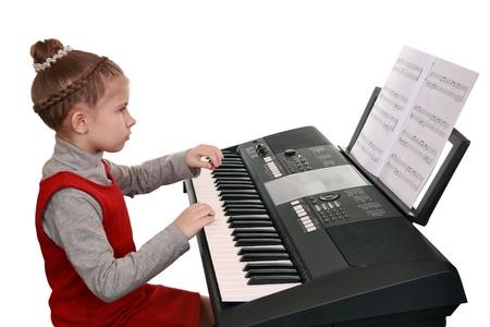 Una niña jugando con un teclado digital