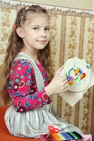 Girl with a home-made embroidery in the hands of