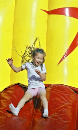 resilient: Girl with inflatable slides slides  Stock Photo