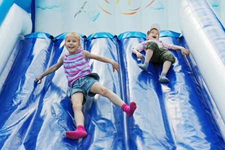 springy: Cheerful children play with inflatable slides  Stock Photo
