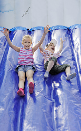 Funny kids and off the inflatable slides Stock Photo - 29435014
