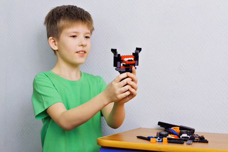 them: Boy holding a robot constructed them Stock Photo