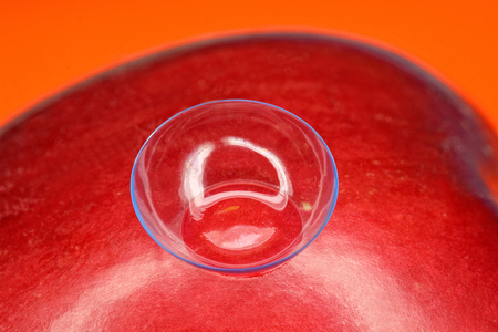 shortsightedness: Soft contact lens on the surface of the red apple