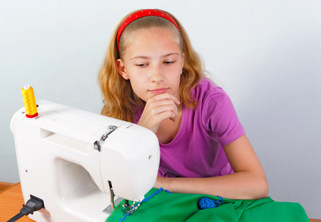 Girl teenager comes up with a new model of sewing clothes on a sewing machine Stock Photo