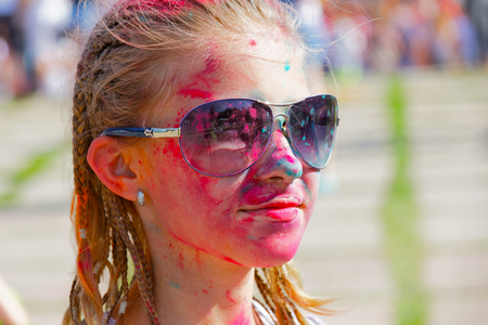 Portrait of a joyful girl in stains from dry paint at a festival of paints