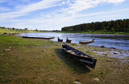 Moored to the shore near the village of long classic wooden boats of the Siberian Mansi people on the river North SOSva