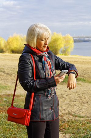 Care for your health. A middle-aged woman looks and evaluates the results of its activity on this day on fitness bracelet and smartphone