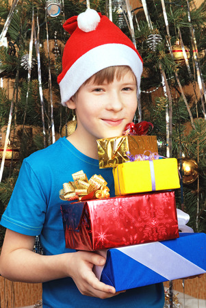 Teen in Christmas cap holding gifts Stock Photo
