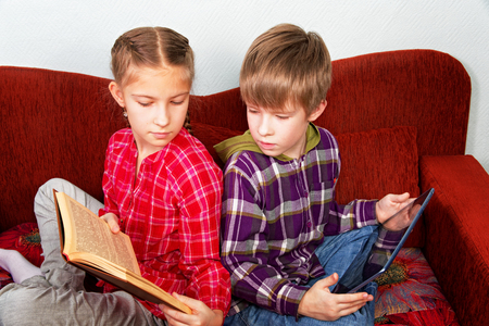 The girl proves to his brother the advantage of basic books before reading from an electronic tablet Banco de Imagens