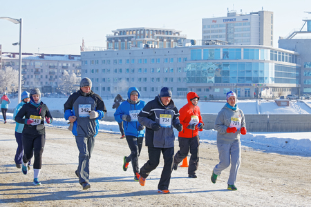 Mens and womans with thick hoarfrost on their hats run during the Christmas half-marathon in Omsk at minus 23 Editorial