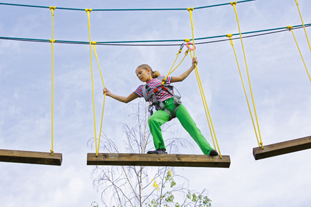 A teenager girl walks neatly on the boards on a rope park