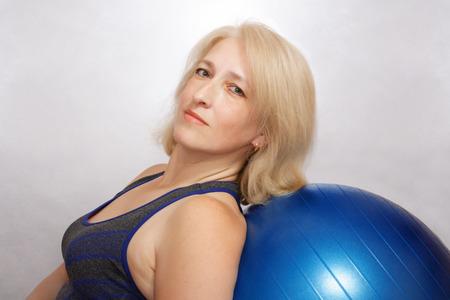 Een vrouw van middelbare leeftijd voert een oefening uit in Pilates, leunt op fitball. Betaalbare sporten thuis Stockfoto