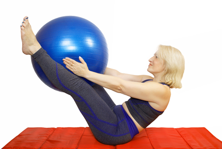 A middle-aged woman performs a physical exercise from Pilates,compresses kicking the ball the fitball and raises them . Exercise for elasticity and body shaping, weight loss