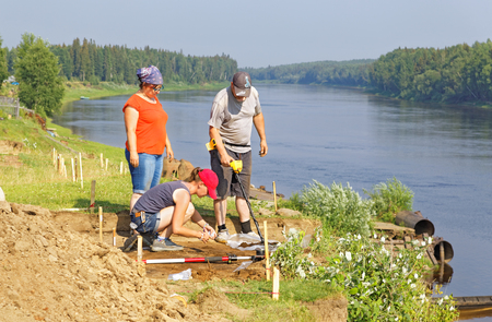 Three archaeologists are looking for small metal objects in the scattered soil with the help of a metal detector