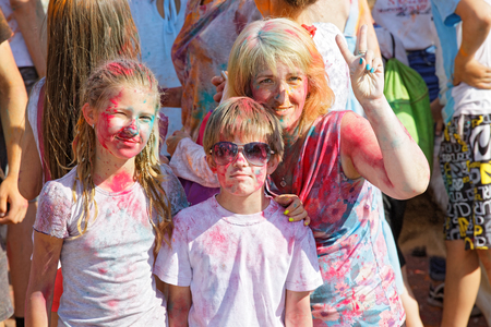 Mother and her children are having fun at the annual paint festival in park