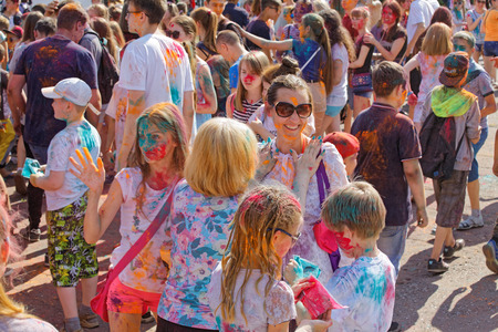 A large group of people of all ages have fun at the festival of paints Holi