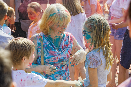 Mother and her children are having fun at the annual paint festival