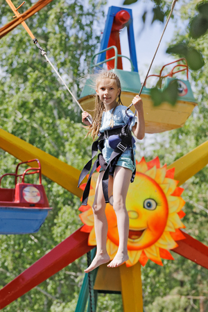 Girl jumping on a kangaroo trampoline in the amusement Park
