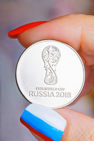Commemorative coin in honor of the World Cup in the womens hand. The finger nails are painted in the color of the flag of Russia