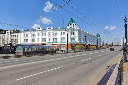 Omsk, Russia. Modern street in the background of a building built in the 19th century Editorial