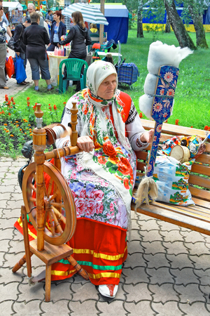 Russian old woman twists a thread on an ancient wooden spinning wheel. Disappearing art... Editorial