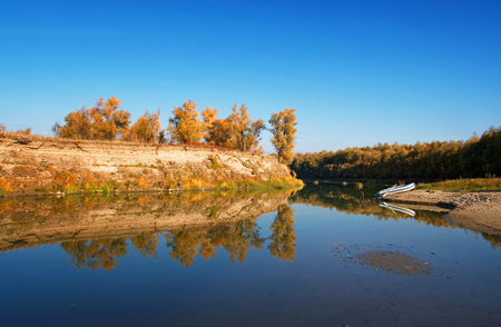 Autumn Siberian landscape-a lonely inflatable boat moored on the river bank