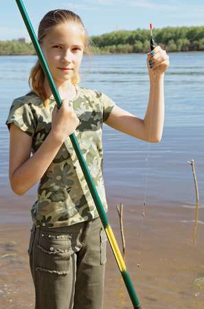 Happy teen girl preparing to fishing on the river Foto de archivo