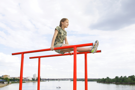 Smiling teenage girl doing gymnastic exercises on uneven bars in city conditions outdoors