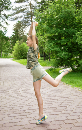 Slender teen girl with ice cream in hand dancing in the park enjoying the coming vacation. Choreographic exercises on the alley among the trees