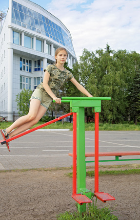 Teen girl trains on a swinging simulator outdoors Foto de archivo