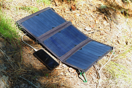 The folding solar panel lies on the surface of the forest soil and charges the smartphone. Convenience for traveling and long walks away from traditional energy sources Foto de archivo