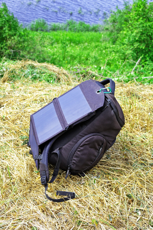 A compact solar panel is attached to the backpack. Convenient device for charging gadgets while traveling or on a walk outdoor