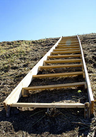Wooden ladder on a steep hill as a symbol of human development