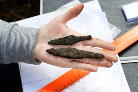 Archeology: rusty arrowheads of medieval arrows lie on the hand of a scientist