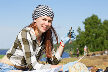 Girl archaeologist demonstrates the find during the field expedition