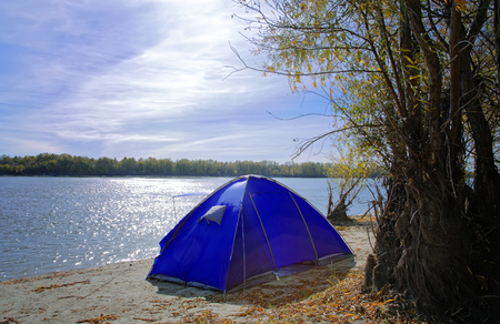 Autumn morning landscape, tent on the river bank