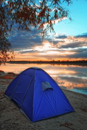 Tent by the river on the background of an autumn sunrise Foto de archivo