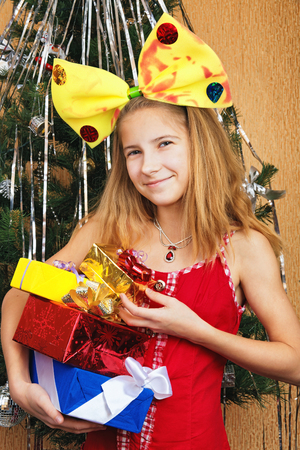 Beautiful teen girl in funny costume holding gift boxes