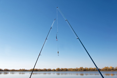 Two spinning rods on the background of the bank of the autumn river