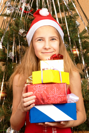 Teen girl in Christmas cap holding gifts