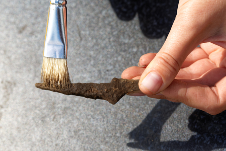 Archeology: cleaning the rusty tip of an ancient arrow from the soil