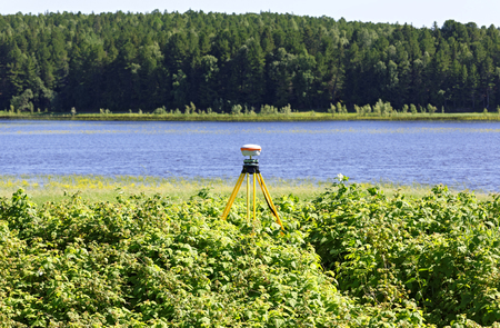 Geodetic GNSS receiver installed on the river bank works autonomously Foto de archivo