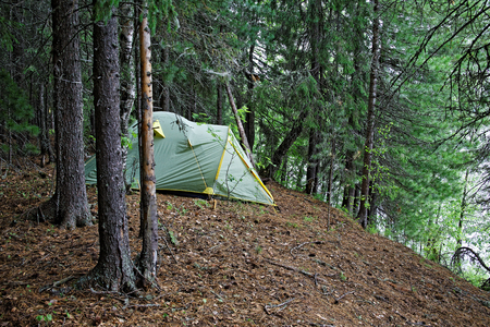 Tent installed on the steep bank of a wild Siberian river Foto de archivo