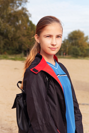 Teenager girl in a raincoat and backpack walk outdoors