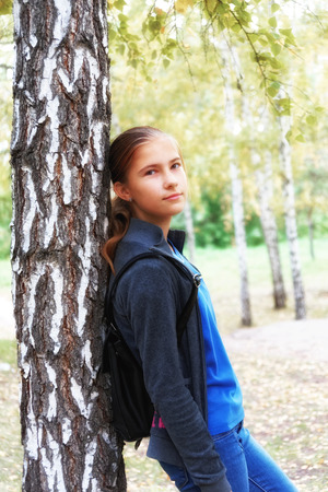 Romantic mood in a teen girl in an autumn birch grove. Soft focus image