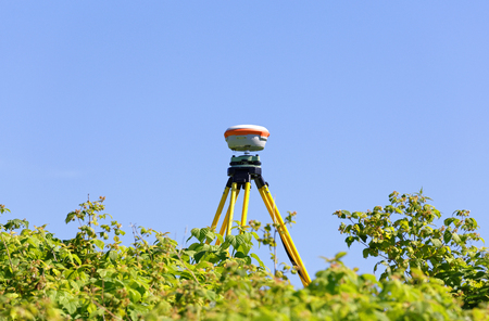 A modern geodesic receiver operates autonomously in the field among wild raspberry thickets