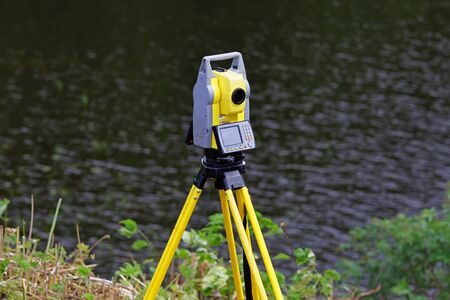 The total station is installed on a tripod, use in the field to determine the coordinates. In the background - the Siberian river
